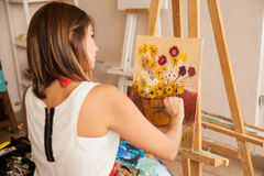Female artist painting some flowers Royalty Free Stock Photo