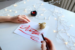 Female artist paints bright inscription on paper sheet with ink Royalty Free Stock Photos