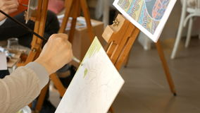 Female artist paints picture artwork in art studio. Female artist paints a picture oil painting artwork drawing on canvas easel in art studio. Student girl stock video footage