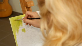Female artist paints picture artwork in art studio stock video
