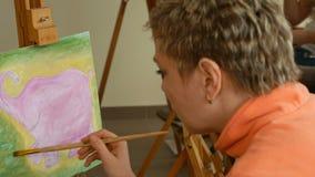 Female artist paints picture artwork in art studio stock video footage