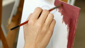 Female artist paints picture artwork in art studio. Female artist paints a picture oil painting artwork drawing on canvas easel in art studio. Student girl stock video