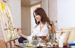 Female artist paints picture on canvas Royalty Free Stock Photos