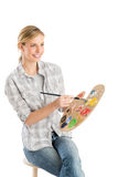 Female Artist With Palette And Paintbrush Sitting On Stool Royalty Free Stock Photography