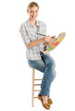 Female Artist With Palette And Paintbrush Sitting On Stool Stock Photos