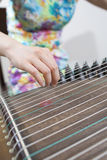 Female artist playing  guzheng,a Chinese old 21-or 25-stringed p Stock Photos