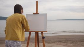 Female artist preparing canvas for painting on the bank of the river. stock video footage