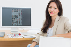 Female artist sitting at desk with computer in office Royalty Free Stock Photo