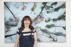 Female Artist Standing In Front Of Large Painting Royalty Free Stock Images