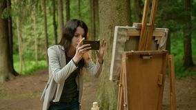 Female artist takes a picture of her painted picture on a smartphone. Beautiful tall brunette paints a landscape in an open air in the forest and taking a stock video