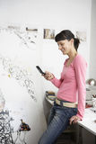 Female Artist Text Messaging On Cell Phone Royalty Free Stock Photos