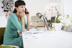 Female Artist Using Cell Phone At Desk Stock Images