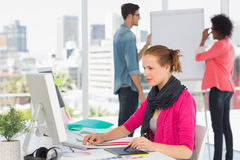 Female artist using graphic tablet with colleagues at office. Side view of a female artist using graphic tablet with colleagues behind at the office Stock Images