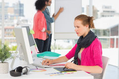 Female artist using graphic tablet with colleagues at office. Side view of a female artist using graphic tablet with colleagues behind at the office Royalty Free Stock Images