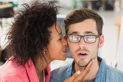 Female artist whispering into colleagues ear Royalty Free Stock Image