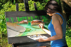 Female artist working on nature painting Stock Photography