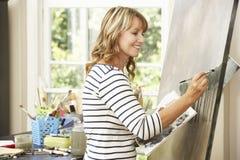 Female Artist Working On Painting In Studio Stock Photo