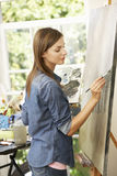 Female Artist Working On Painting In Studio Royalty Free Stock Images
