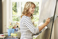 Female Artist Working On Painting In Studio Royalty Free Stock Photography