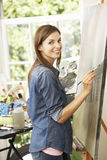 Female Artist Working On Painting In Studio Stock Photo