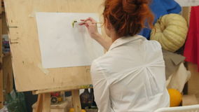 Female artist working on watercolor painting in studio stock video