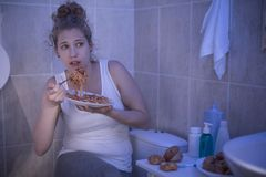 Female ashamed of her illness. Picture of female ashamed of her illness eating in bathroom Stock Photos