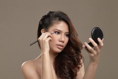 Female asian applying eye shadow Stock Photo