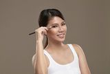 Female asian applying eye shadow royalty free stock photography