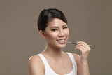 Female asian applying lipgloss stock images