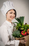 Female Asian Chef with Paper Bag of Vegetables Royalty Free Stock Images