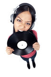 Female Asian DJ biting a record. A wide angle full body shot of a female Asian DJ biting a record and wearing headphones Stock Image