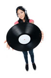 Female Asian DJ holding a record out. A wide angle full body shot of a female Asian DJ holding a record far in front of her and wearing headphones Royalty Free Stock Photography
