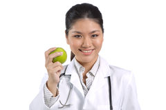 Female Asian doctor holding an apple. Royalty Free Stock Photography