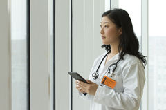 Female Asian doctor holding a tablet Royalty Free Stock Photos