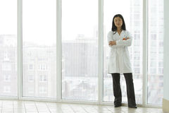 Female Asian doctor standing with arms crossed Stock Images