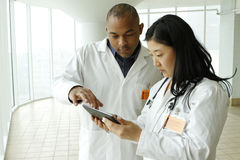 Female Asian doctor talking with African American doctor with tablet Royalty Free Stock Images