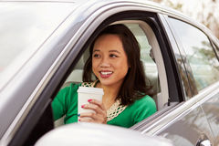Female Asian driver drinking take-away drink in a car Royalty Free Stock Photo