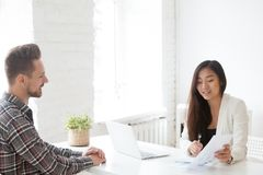Female Asian employer mentoring male subordinate on financial is. Female asian employer talking about financial statistics with caucasian male employee royalty free stock images