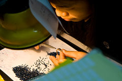 Female asian goldsmith puts jewelry Stock Image