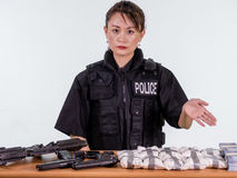Female Asian police officer showing seized goods Stock Photography