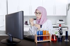 Female Asian researcher works in the lab. Female Muslim researcher works in the lab while dripping a chemistry fluid with a pipette and looking at a computer Stock Image