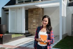 Female asian student in front of her house. Portrait of female asian student in front of her house ready to go to college royalty free stock photography