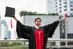 A female Asian student in graduation gown holding the diploma an stock photos