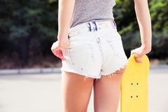 Female ass in shorts with skateboards outdoors Royalty Free Stock Photos