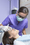 Female assistant and patient. Young female assistant is working with the aspirator in a young female patient at the dental cabinet Royalty Free Stock Images