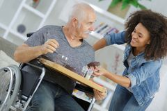 Female assistant with senior man in wheelchair at home royalty free stock images