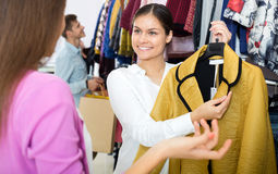 Female assistant serving happy customers. Asking in clothing boutique Stock Photos