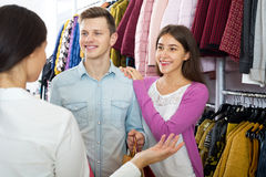 Female assistant serving happy customers Stock Images