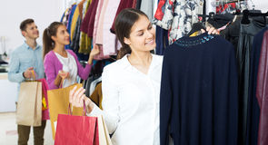 Female assistant serving happy customers. Attractive women customers chooses liked things in the boutique Stock Photography