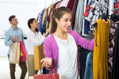 Female assistant serving happy customers. Attractive young female shopper chooses liked things in the boutique Royalty Free Stock Photos